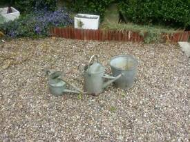 Old steel watering cans and bucket