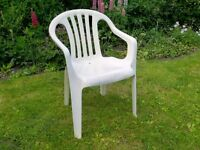 Two stackable white garden chairs