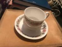 Cup and saucer with a little oil lamp