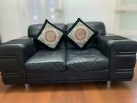 Black leather sofas and matching stool