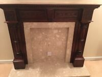 Ornate wooden fireplace surround with marble inlay and base.