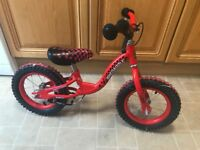 1 red balance bike and 1 pirate bike with stabilisers