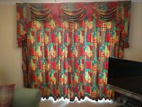 Multi colored patterned tie back curtains with a pelmet, dressed with swags and tails finish
