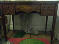 Vintage wood desk with blotter to, drawers, ornate decoration and wheeled feet
