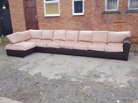 Superb BRAND NEW very very large corner sofa. Brown leather base.fabric cushions.can deliver