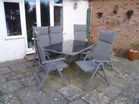 Glass top patio table with six chairs, cushions and parasol