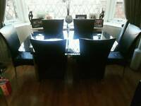 Beautiful black glass dining table and 6 black faux leather chairs
