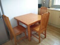 Square solid wood dining table with four chairs