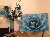 Blue themed picture and flower arrangement.