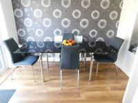 Black glass extending dining room table with 4 chairs.
