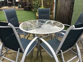 Round glass table and 5 chairs which also recline as sunloungers. Stack for easy storage