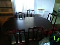 Dark wooden dining table with 5 upholstered chairs.