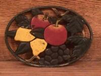 Vintage cast iron trivet with a pretty fruit motif