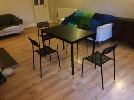 Black dining table with four chairs