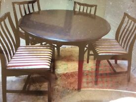 Stag Minstrel round dining table which can be extended to oval with four chairs