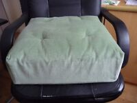 A Green Velor Booster Cushion