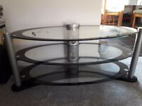 Oval Black and clear glass with silver TV stand.