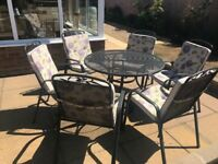 Round garden table and six stakable chairs