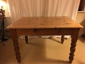 Solid pine kitchen dining table with turned legs and cutlery drawer.