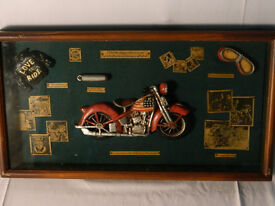 Wall plaque with various motorbike related memorabilia