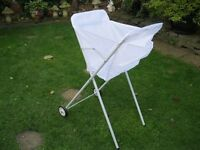 Laundry cart on wheels with pouch on front for pegs.