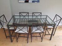 Lovely glass dining table with 6 chairs and cushions