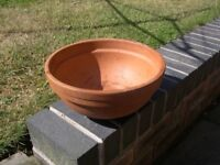 A bowl shaped terracotta planter with ribbed sides.