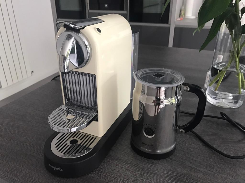 Cream nespresso coffee maker with milk frothier.