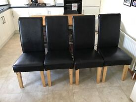 Four Black leather effect dining chairs