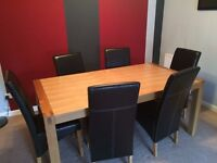 Sold oak dining table and 6 faux leather chairs