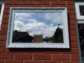 A lovely pretty beveled mirror in light grey with darker grey highlights