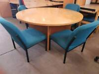 Large round meeting table and green chairs