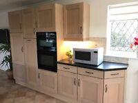 Light oak kitchen units with black worktops