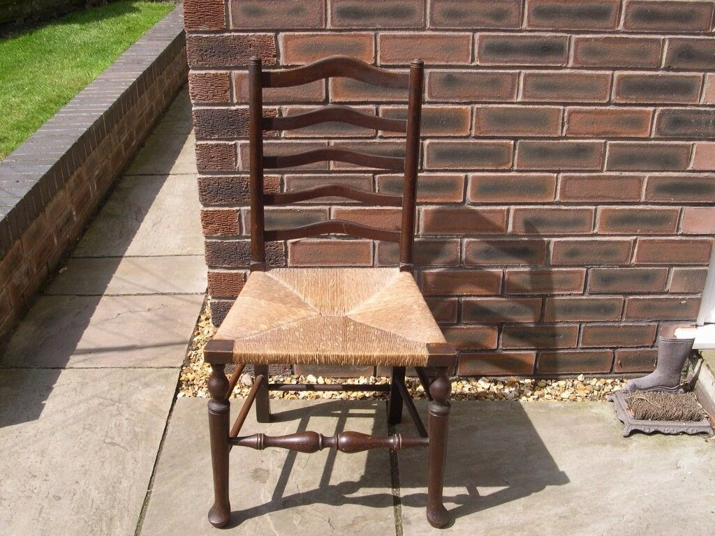 A vintage Hands & Sons ladder back chair with rush seat.