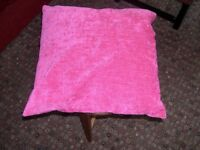 An attractive mid pink coloured cushion.