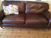 brown leather settee on wooden castors