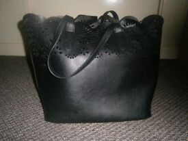 Large black handbag with separate inner bag and cut out detail.