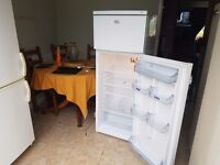 family size Whirlpool fridge with freezer compartment at the top.