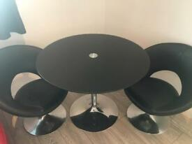 Black glass table with two bucket seats