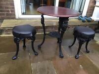 Cast iron pub table and 2 cast iron stools .
