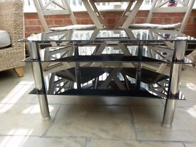 "Black glass T V table ,Take T V up to 40""wide As new."