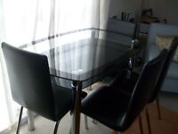 Glass table with stainless steel legs and 4 black faux leather chairs to match.