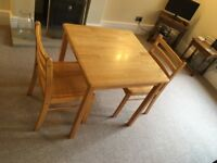 Two seater table and matching chairs. Solid wood and substantial.