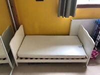 Toddler single bed with mattress and mattress protector.