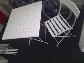 White metal folding table and four chairs