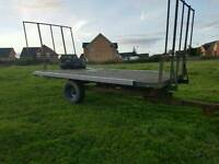 Tractor flat bed tipping bale trailer with front and rear bale holders