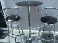 Glass top tall round table and two swivel chair/bar stools.