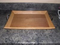 An attractive wooden tray with metal handles.