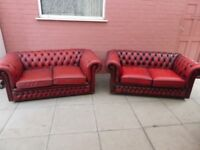 A Pair Of Red Leather Two Seater Chesterfield Sofas
