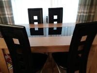 Oak effect table with glass centre and 4 black chairs.